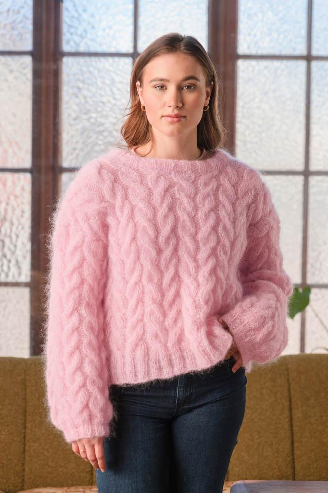 Strikkepakken inneholder mønster og garn fra Dalegarn til Melanita genseren som strikkes i Myk Påfugl. Her i fargen rosa. Modellen i halvfigur, ser rett inn i kamera.