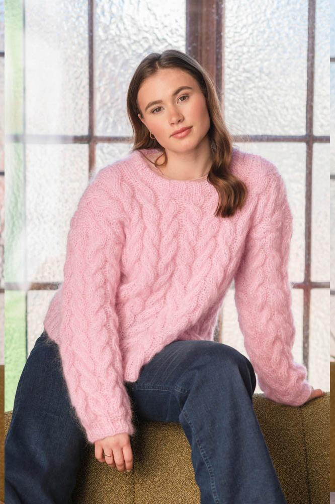 Strikkepakken inneholder mønster og garn fra Dalegarn til Melanita genseren som strikkes i Myk Påfugl. Her i fargen rosa. Modellen sitter.