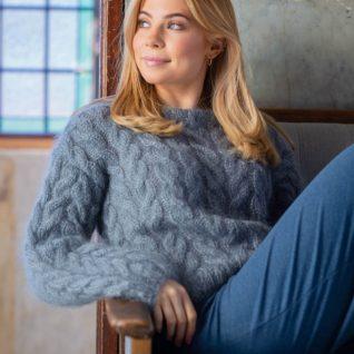 Strikkepakken inneholder mønster og garn fra Dalegarn til Melanita genseren som strikkes i Myk Påfugl. Her i fargen stålgrå. Modellen sitter i en sofa og ser til venstre.