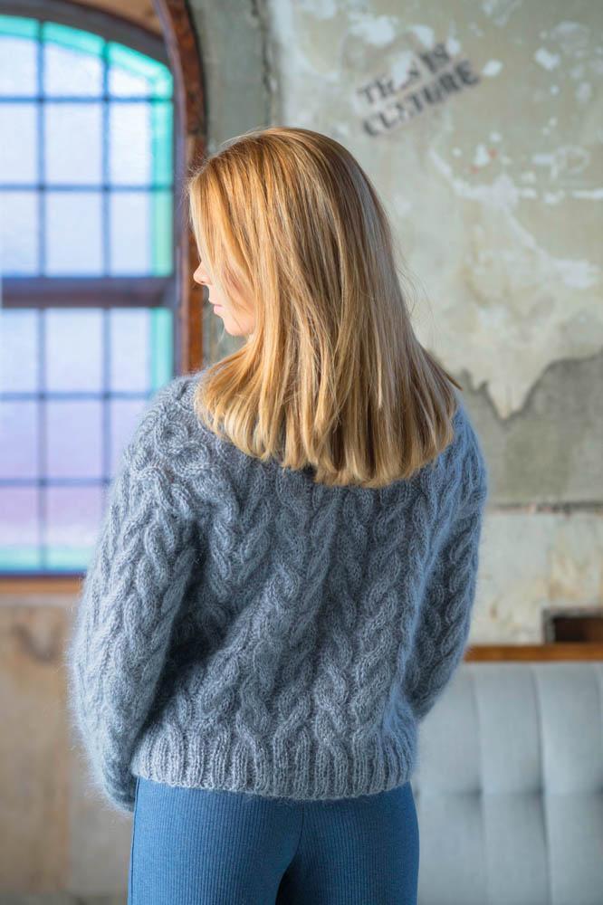 Strikkepakken inneholder mønster og garn fra Dalegarn til Melanita genseren som strikkes i Myk Påfugl. Her i fargen stålgrå. Vi ser modellen bakfra.
