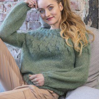 Strikkepakken inneholder mønster og garn fra House of Yarn til Jackie genser strikket i Myk Påfugl. Modellen sitter avslappet i en sofa.
