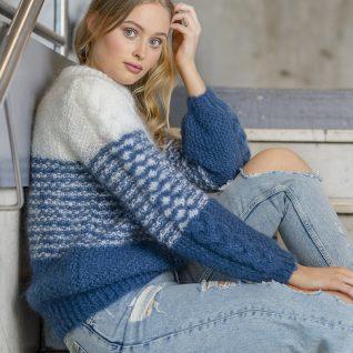 Strikkepakken inneholder mønster og garn fra House of Yarn til Poppy genser strikket i Myk Påfugl. Modellen sitter i en trapp.