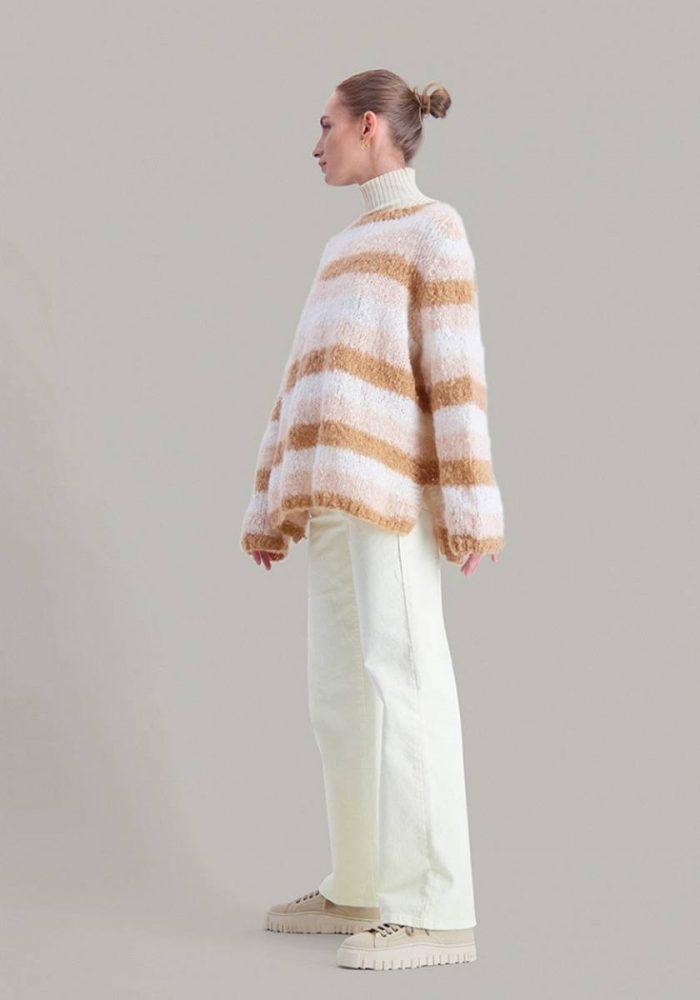 Strikkepakken inneholder mønster og garn fra Skappel Classic som strikkes i Suri alpakka garn. Her ser vi modellen i helfigur og hun står sidelengs mot venstre.