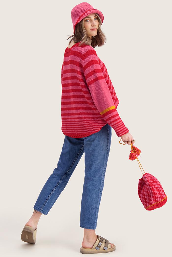 Strikkepakken inneholder mønster og garn til Mette genser fra Skappelstrikk og Ida Broen. Designet i bomullsgarnet Frisk. Modellen i rød og rosa. Ses fra siden.