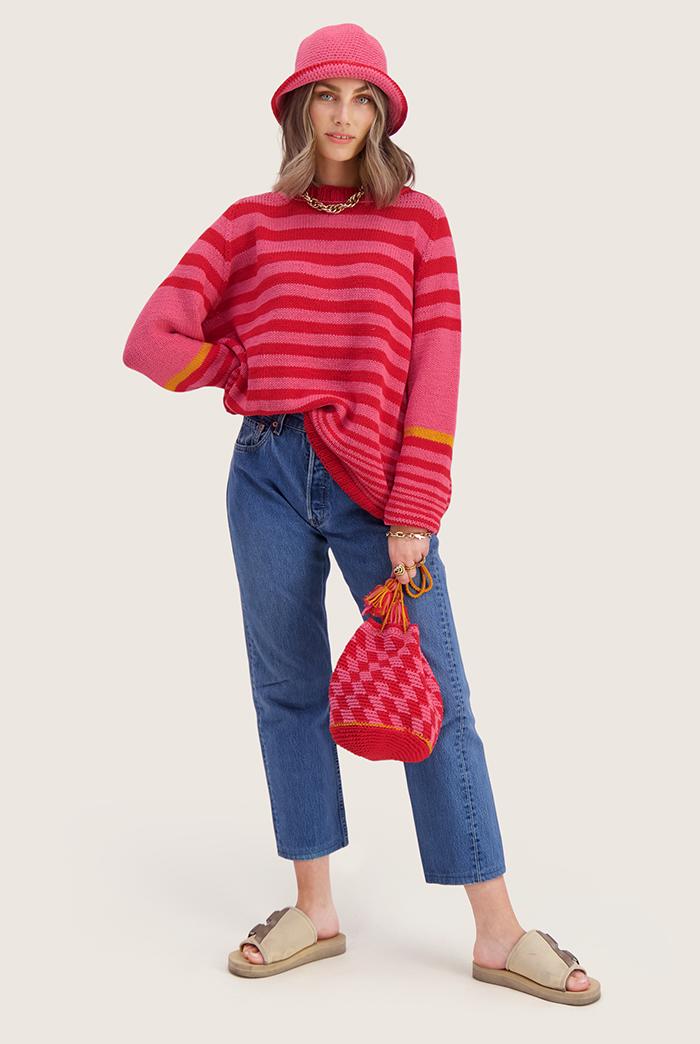 Strikkepakken inneholder mønster og garn til Mette genser fra Skappelstrikk og Ida Broen. Designet i bomullsgarnet Frisk. Modellen i rød og rosa.