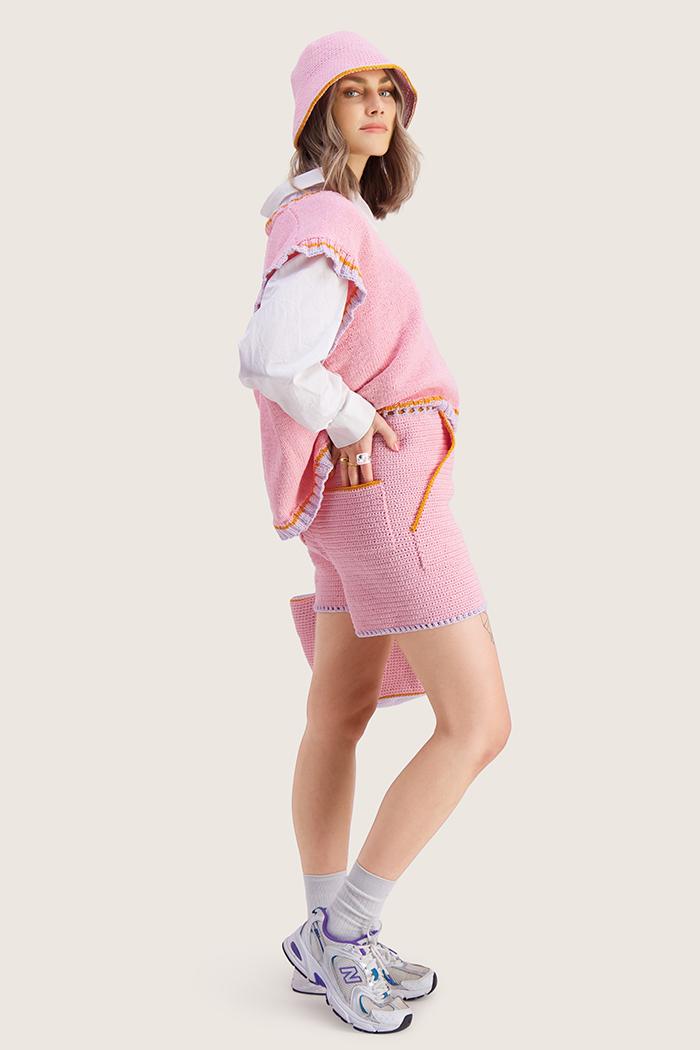 Strikkepakken inneholder mønster og garn til Stjerna vest fra Skappelstrikk og Ida Broen. Designet i bomullsgarnet Frisk. Her i fargen rosa. Modell sidelengs