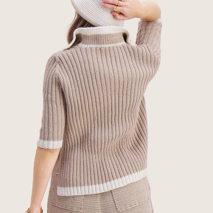 Strikkepakken inneholder mønster og garn til Syrin genser fra Skappelstrikk og Ida Broen. Designet i bomullsgarnet Frisk. Modellen ses bakfra.