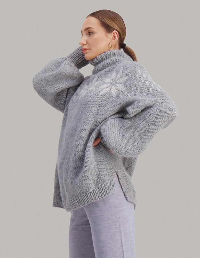 Strikkepakken Duggfrisk genser fra Skappel Classic. Bildet viser modellen i halvfigur. Modellen står i front og ser inn i kamera. Begge hendene hviler bak nakken. Fargen på genseren er grå og naturhvit. Her ser vi modellen fra siden.
