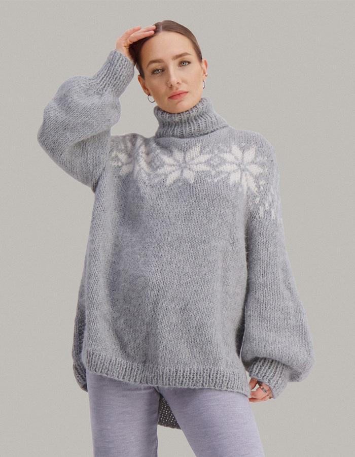 Strikkepakken Duggfrisk genser fra Skappel Classic. Bildet viser modellen i halvfigur. Modellen står i front og ser inn i kamera. Begge hendene hviler bak nakken. Fargen på genseren er grå og naturhvit.