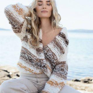 Strikkepakken fra Camilla Pihl inneholder oppskrift og garn til Crocus jakke i Fnugg garn. Farge natur.